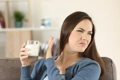 Vrouw die een glas melk weigeren stock foto's