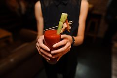 Vrouw die een glas van alcoholische cocktailbloody mary binnen houden stock fotografie