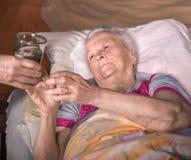Vrouw die een glas water geven aan de zieke het liggen vrouw Stock Foto
