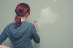 Vrouw die een groene muur schilderen Stock Afbeeldingen