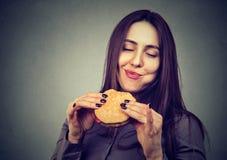 Vrouw die een grote hamburger eten stock afbeelding