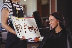 Vrouw die een haarkleur met stilist selecteren royalty-vrije stock fotografie
