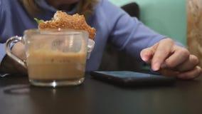 Vrouw die een hamburger eten, koffie drinken en smartphone doorbladeren, die in een snel voedselrestaurant zitten levensstijl stock footage