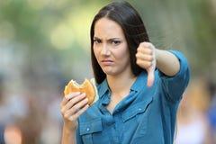 Vrouw die een hamburger met neer duimen weigeren royalty-vrije stock foto