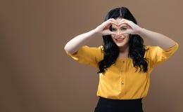 Vrouw die een hart gestalte gegeven gebaar maken royalty-vrije stock afbeeldingen