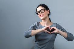 Vrouw die een hart gestalte gegeven gebaar maken royalty-vrije stock foto's