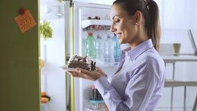 Vrouw die een heerlijk dessert van de koelkast nemen stock foto's