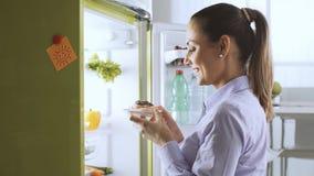 Vrouw die een heerlijk dessert van de koelkast nemen stock afbeeldingen