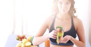 Vrouw die een het drinken glashoogtepunt van verse fruitsalade met een meetlint houden rond het glas Stock Foto