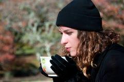 Vrouw die een hete drank drinkt stock afbeelding