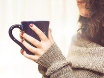 Vrouw die een hete kop van koffie of thee in het ochtendzonlicht houden Stock Foto