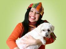 Vrouw die een hond in haar wapens houdt stock foto's