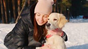Vrouw die een hond in het de winterbos koesteren stock videobeelden