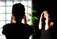Vrouw die een hoofdpijn voor een spiegel hebben stock afbeeldingen