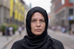 Vrouw die een hoofdsjaal in een stedelijke straat dragen stock foto's