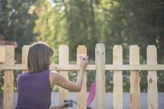 Vrouw die een houten piketomheining vernissen Royalty-vrije Stock Foto