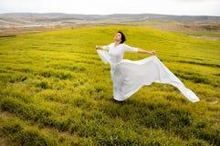 Vrouw die een huwelijkskleding in de weide draagt Royalty-vrije Stock Foto's