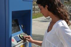 Vrouw die een kaartjesmachine met behulp van Stock Foto's