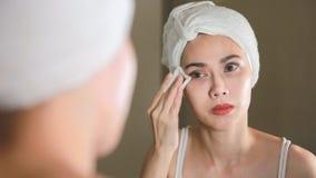 Vrouw die een katoenen stootkussen gebruiken om haar huid voor de spiegel in badkamers schoon te maken stock video