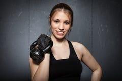 Vrouw die een kettlebell houden en aan camera glimlachen - crossfit fitn Stock Afbeeldingen