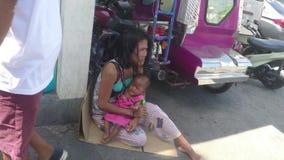 Vrouw die een kind knuffelen die op de stoep liggen die op de straat bedelen stock footage