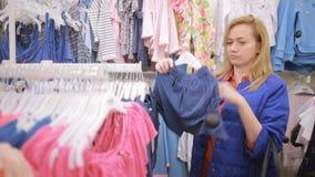 Vrouw die in een kledingsopslag winkelen voor kinderen kinderen` s kleren op hangers stock video