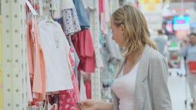 Vrouw die in een kledingsopslag winkelen voor kinderen kinderen` s kleren op hangers stock footage
