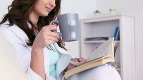 Vrouw die een koffie drinken terwijl zij leest stock videobeelden