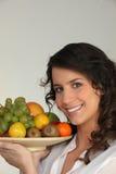 Vrouw die een kom fruit houdt stock foto