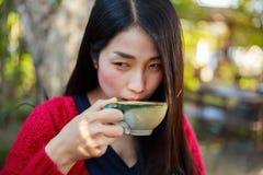Vrouw die een kop van coffe in de tuin drinken Royalty-vrije Stock Foto's