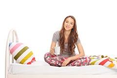 Vrouw die een kop van koffie houden op bed gezet stock fotografie