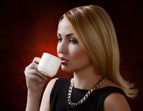 Vrouw die een kop van koffie houdt Stock Afbeelding
