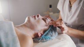 Vrouw die een kosmetische procedure krijgen - maskeer gezichtsmassage bij kuuroordsalon skincare stock afbeeldingen