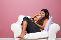 Vrouw die in een leunstoel wordt gezeten die aan muziek luistert royalty-vrije stock afbeeldingen