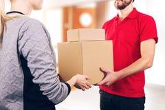 Vrouw die een levering van dozen van de leveringsdienst courie goedkeuren stock afbeeldingen