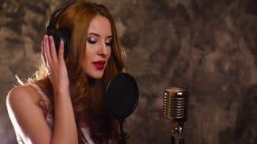 Vrouw die een lied in muziekstudio registreren, langzame motie stock video