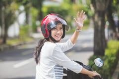 Vrouw die een motor berijden en hand golven royalty-vrije stock afbeeldingen
