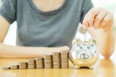 Vrouw die een muntstuk zetten in het geld-doos-sluiten u Royalty-vrije Stock Afbeelding