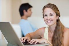 Vrouw die een notitieboekje gebruiken terwijl haar fiance op een bank zit Royalty-vrije Stock Foto