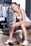 Vrouw die een onderbreking neemt bij de gymnastiek Stock Foto