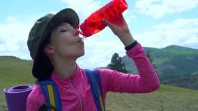 Vrouw die een onderbreking nemen aan drank van waterfles terwijl wandeling stock videobeelden