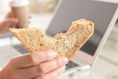 Vrouw die een ontbijtsandwich eten terwijl het werken met laptop royalty-vrije stock fotografie
