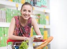 Vrouw die een ontvangstbewijs controleren bij supermarkt Stock Afbeeldingen