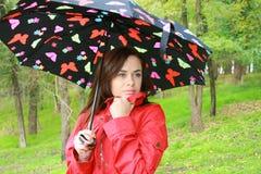 Vrouw die een paraplu houdt Stock Afbeeldingen