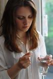 Vrouw die een pil en een glas water houdt Stock Foto