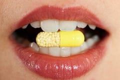 Vrouw die een pil neemt Stock Foto