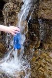 Vrouw die een plastic fles houden die schoon water trekken van de koude lente stock afbeelding