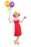 Vrouw die een pruik en houdend huidig en ballons dragen royalty-vrije stock fotografie