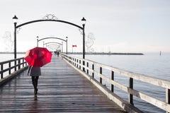 Vrouw die een rode paraplu houden lopend op een regenachtige dag op de pijler Stock Foto's