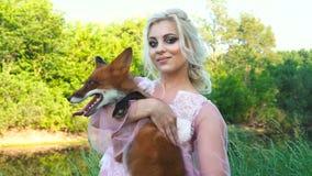 Vrouw die een rode vos, Vossen, in haar die wapens houden door mooie aard worden omringd stock video